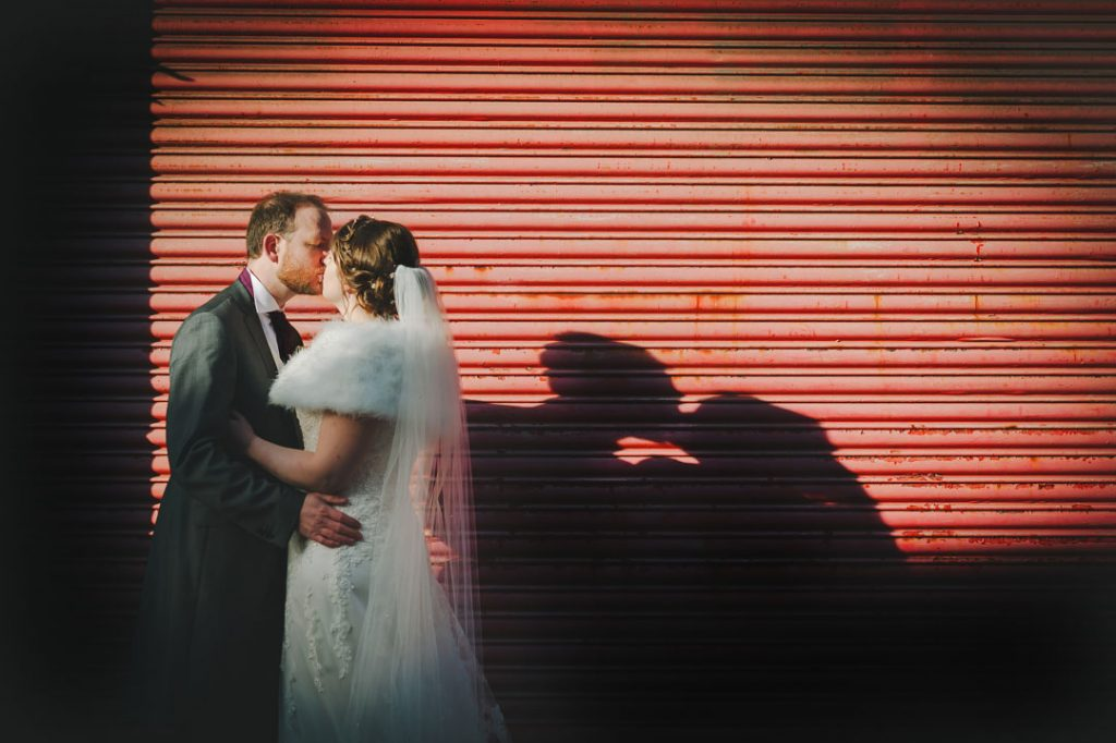 silhouette of bride and groom kissing against red shutter