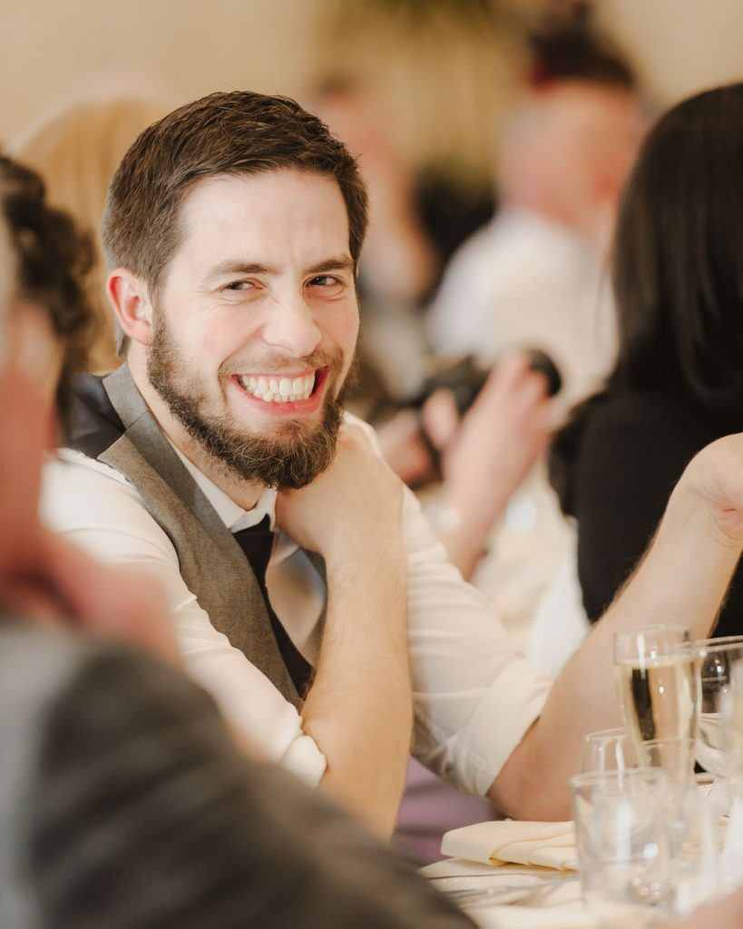 man in waistcoat at wedding reception laughing