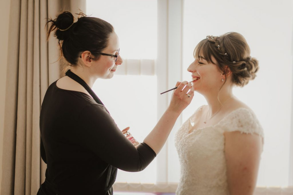 make up artist applying makeup to bride