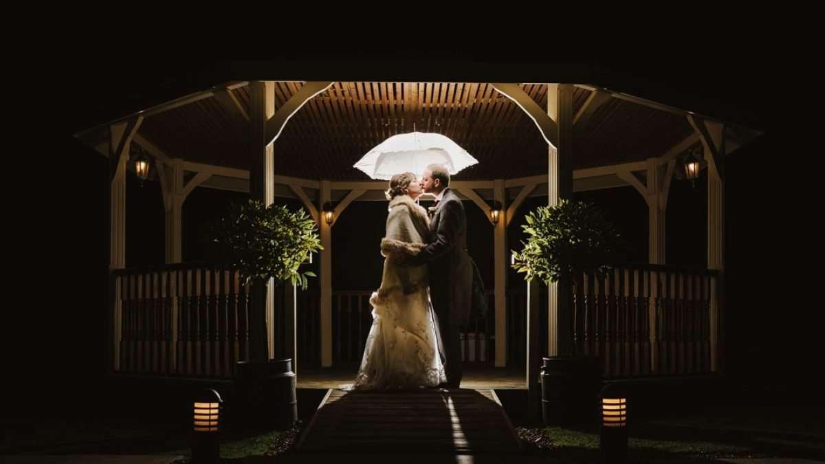 backlit bride and groom holding umbrella