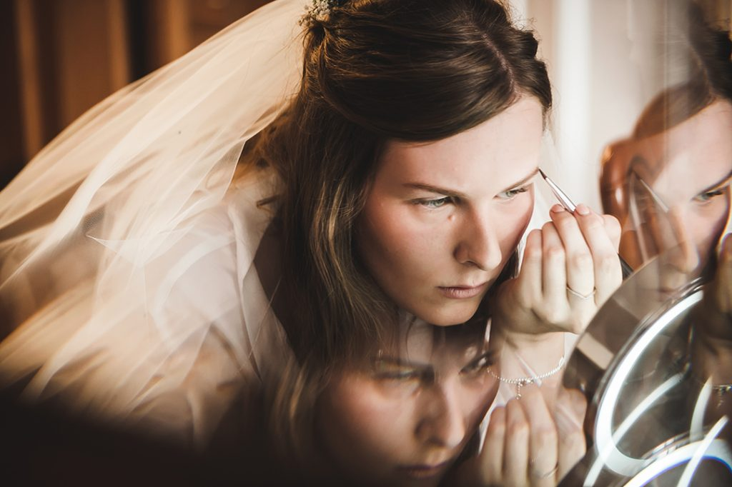 bride applying makeup