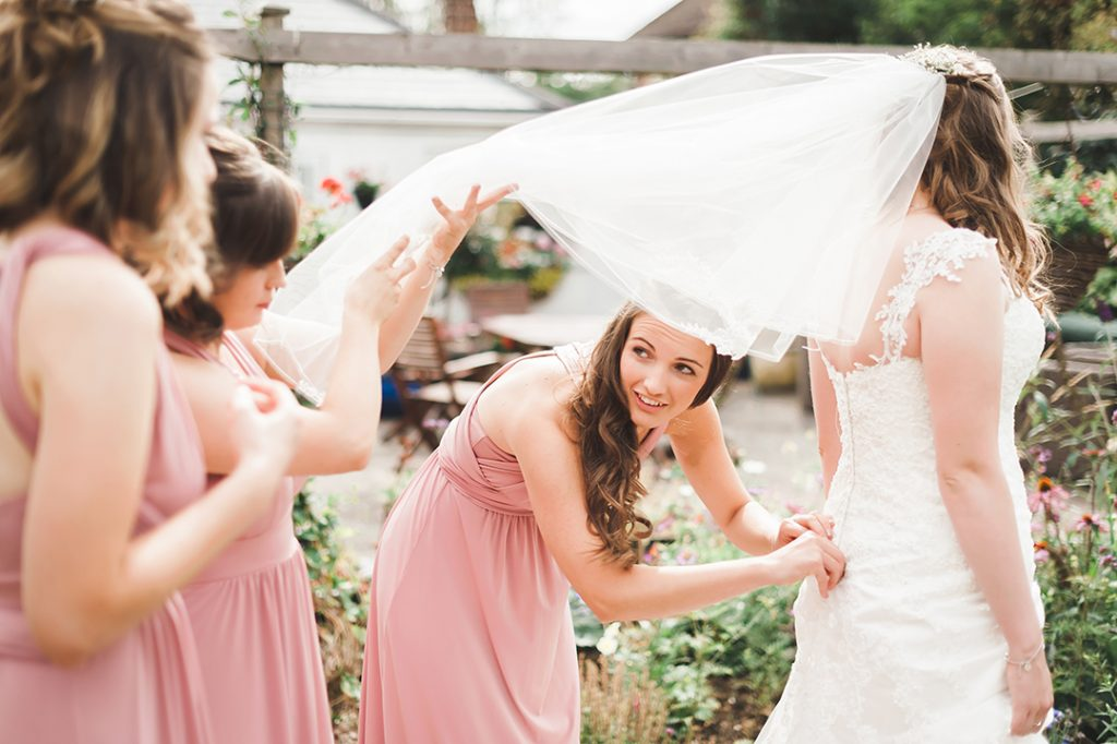 bridesmaids helping bride