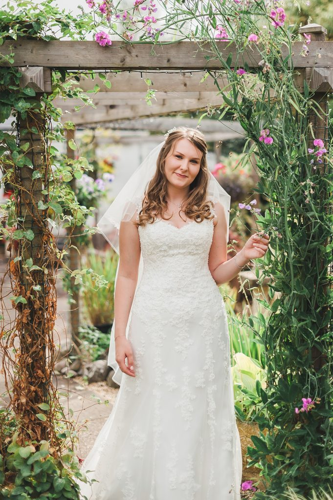 bride in garden with white dress and veil