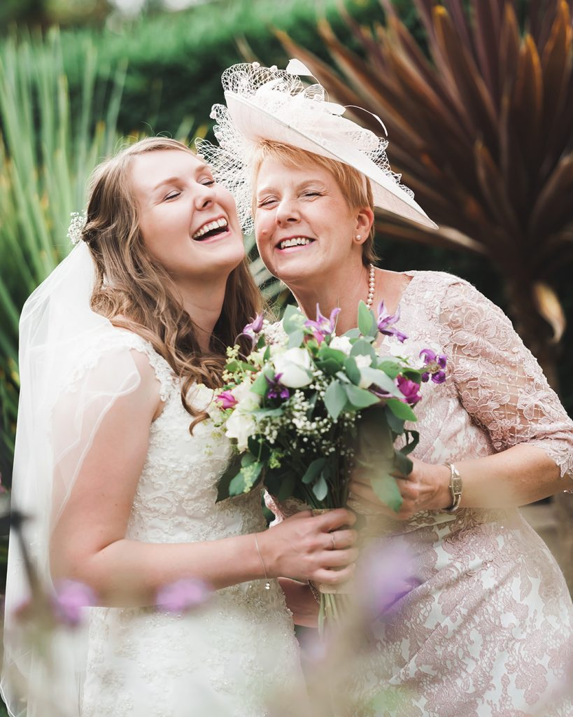 mother of the bride and bride laughing in garden