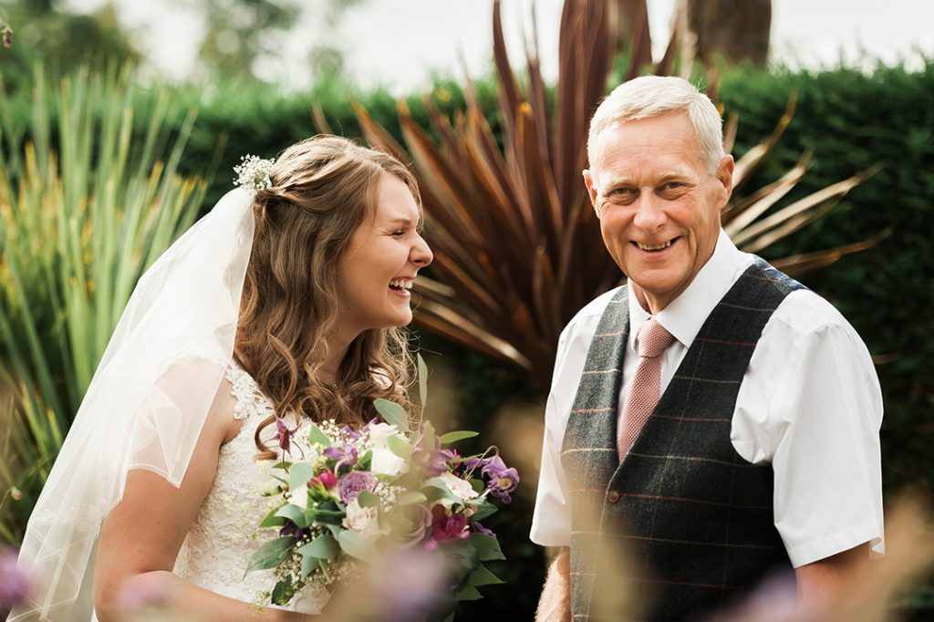 bride laughs at father of the bride
