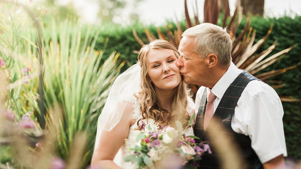 father of the bride kissing bride on cheek