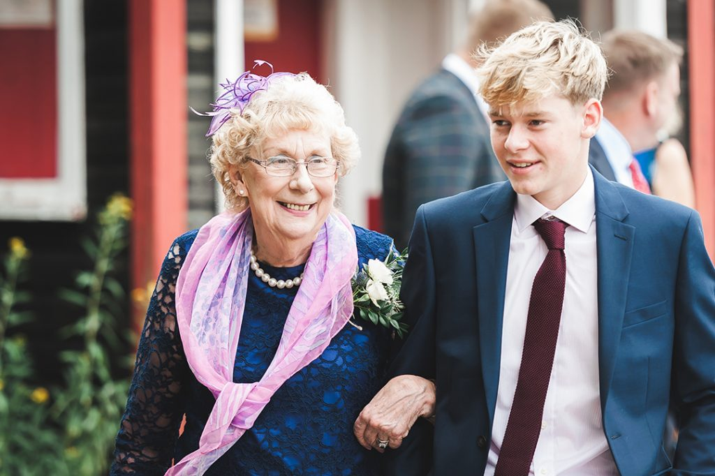 old lady in blue dress and pink scarf at wedding