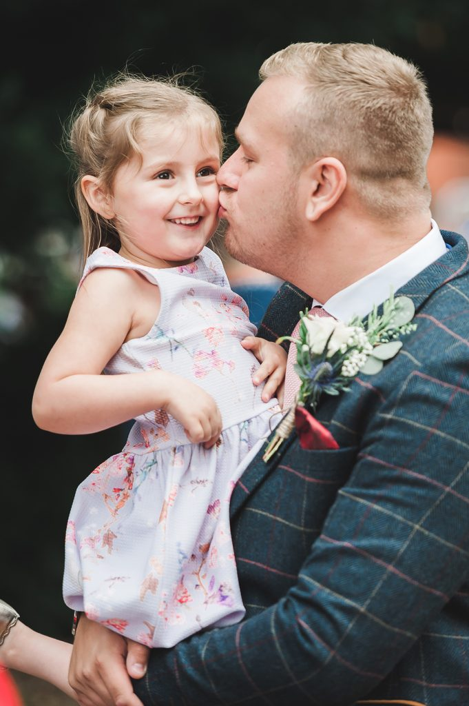 groom kisses little girl