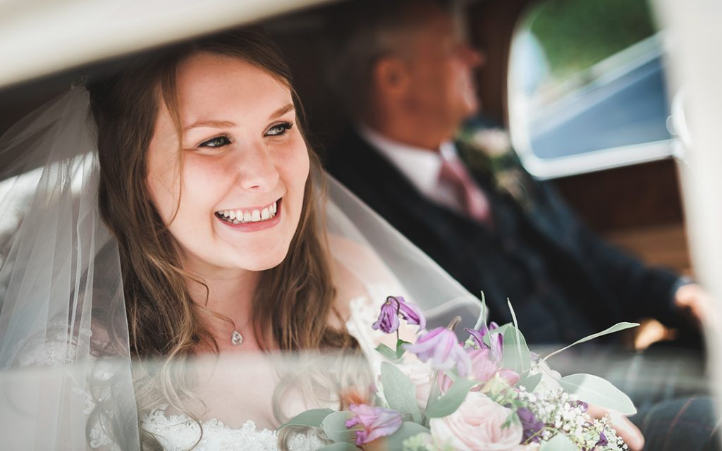 bride smiles inside wedding car