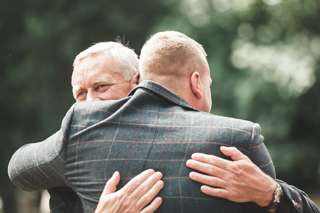 groom hugs father