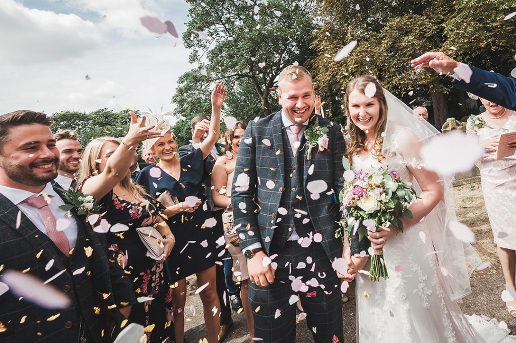 confetti thrown at wedding couple outside of church