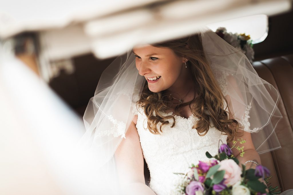 bride in white dress holding flowers looks out of car window