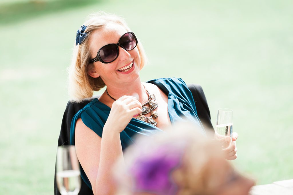 wedding guest in sunglasses and blue dress