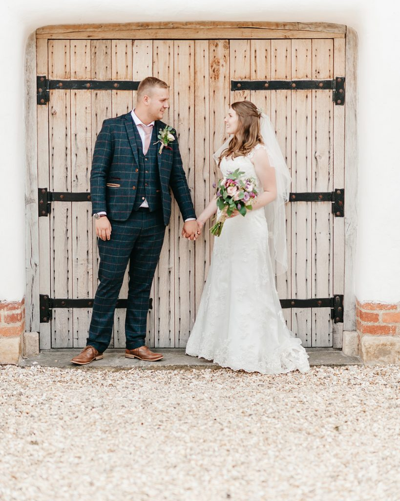bride and groom stood outside of barn door holding hands