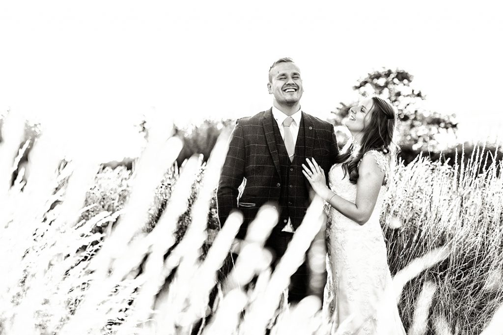 bride and groom photography in field laughing