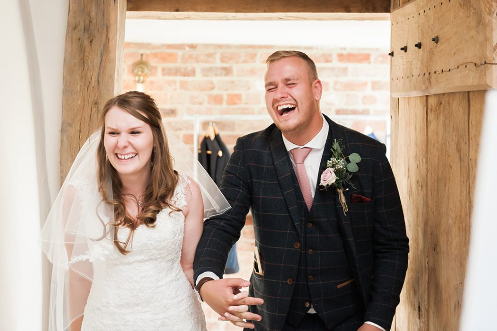 bride and groom enter reception laughing
