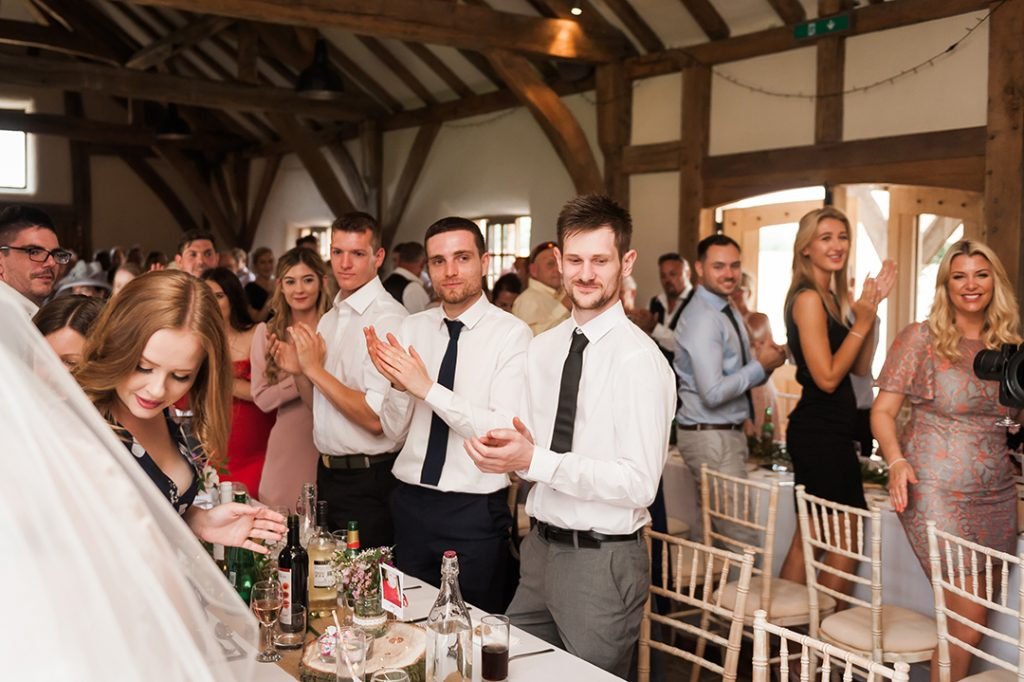 wedding guests clapping at bride and groom