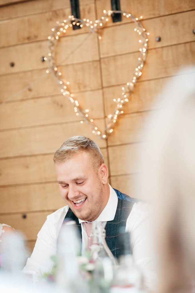 groom laughing beneath love heart lights
