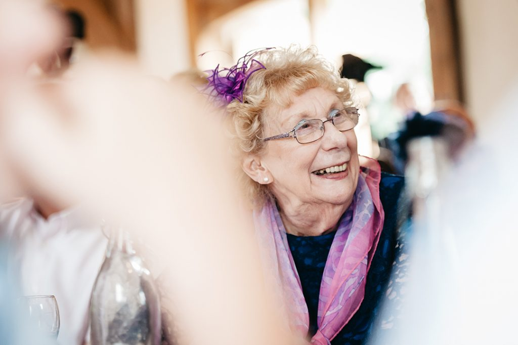 old lady with glasses pink scarf wedding