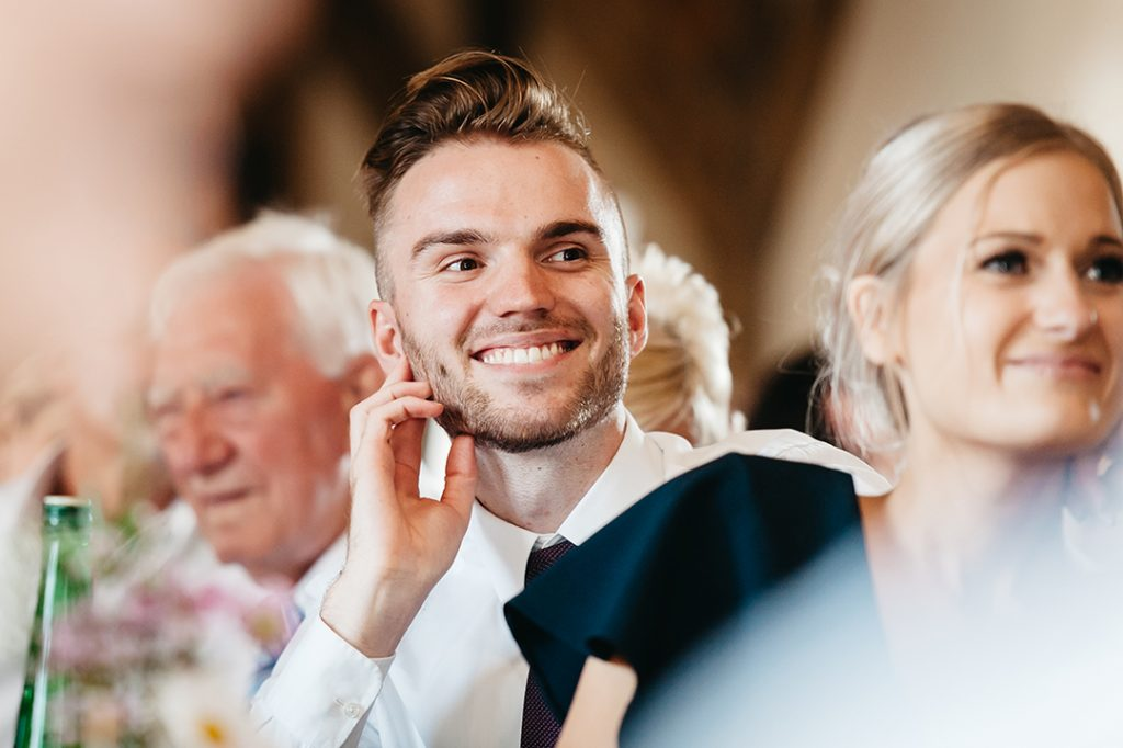 man in white shirt and blue tie smiles at wedding speech
