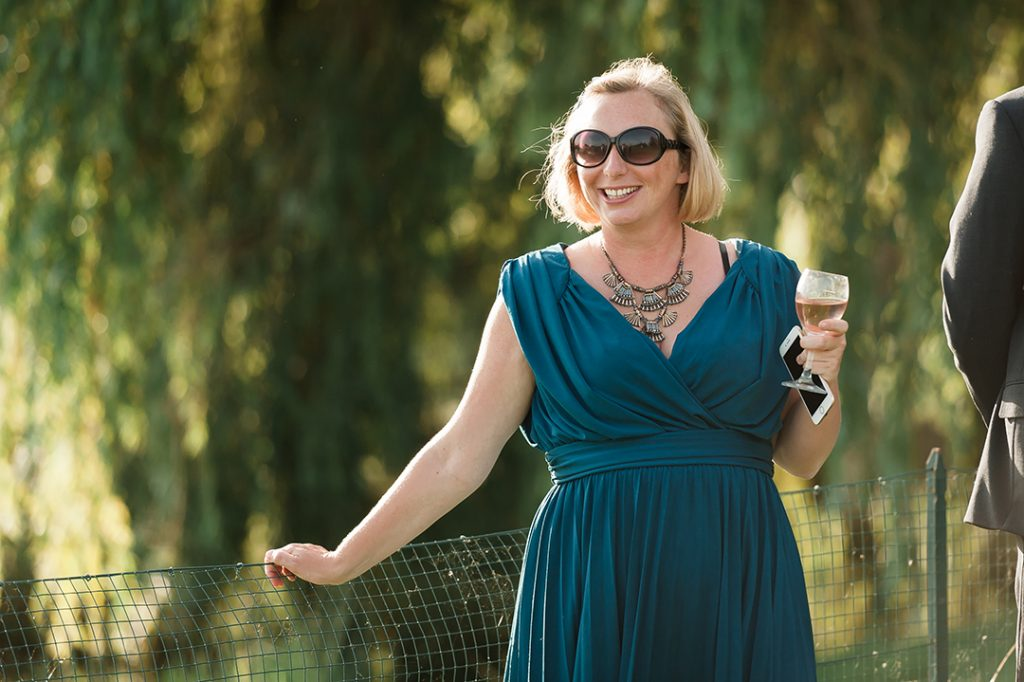 woman in glasses with blue dress holding glass of wine