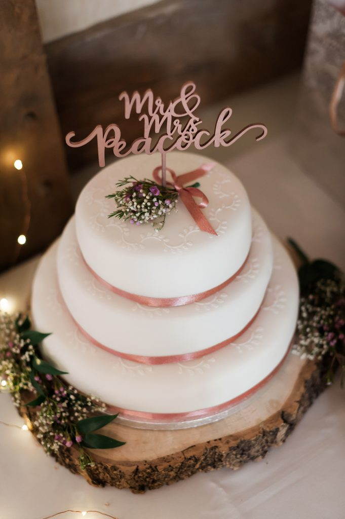 white wedding cake with pink ribbon