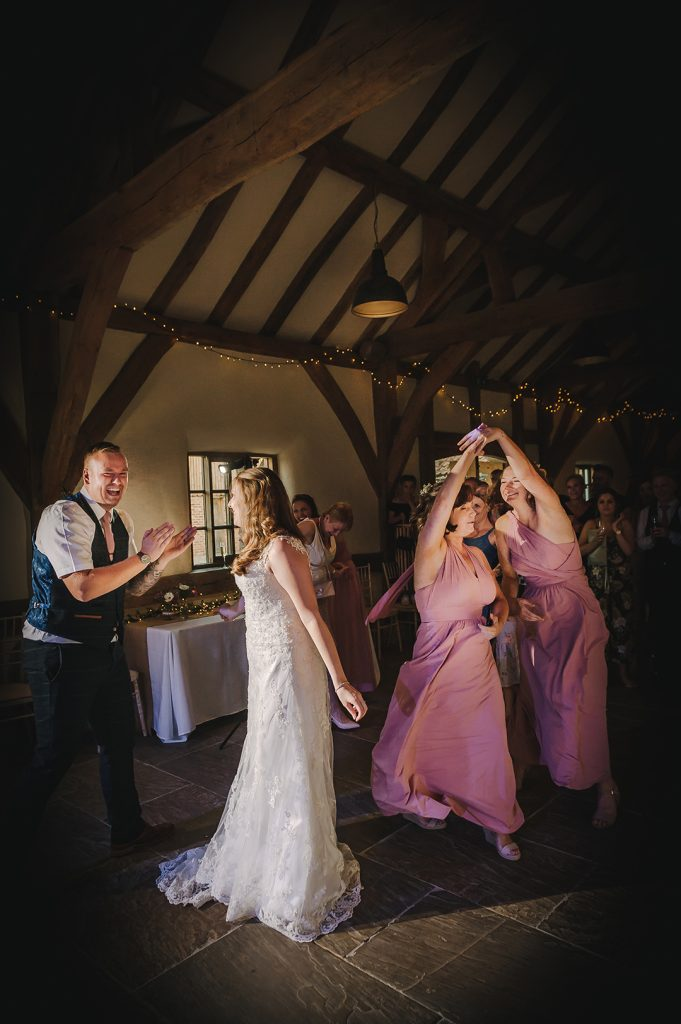 bride and groom dance with bridesmaids in pink dresses