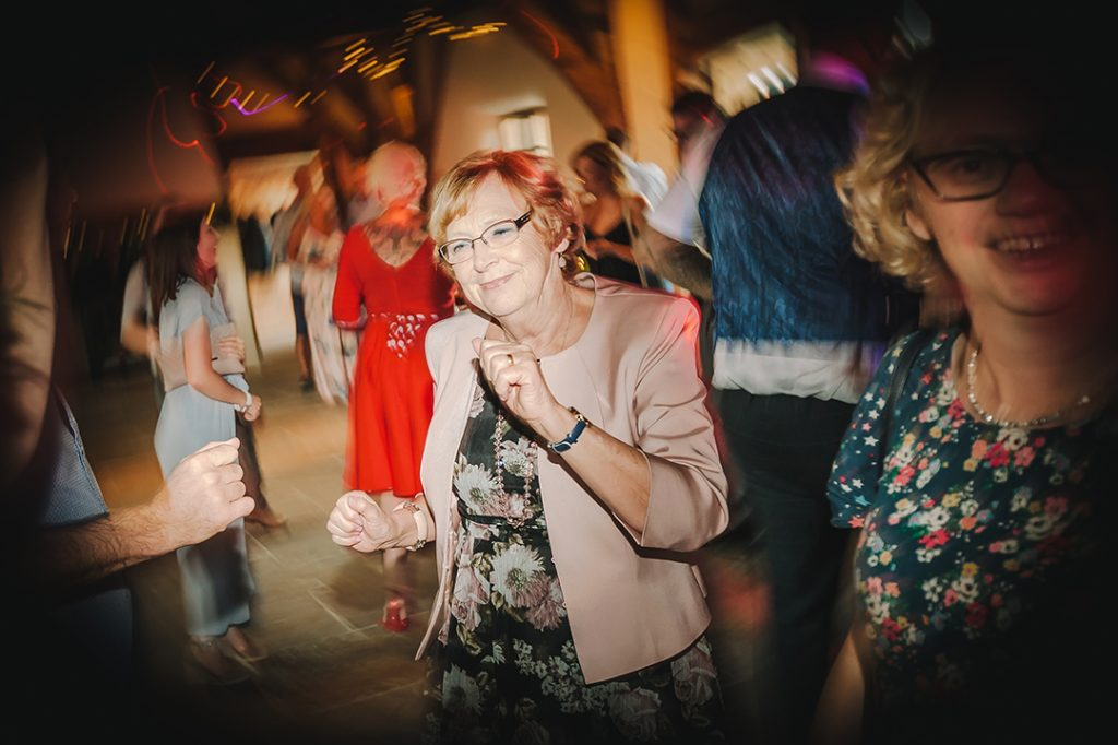 woman dancing in beige jacket at abbey farm wedding reception