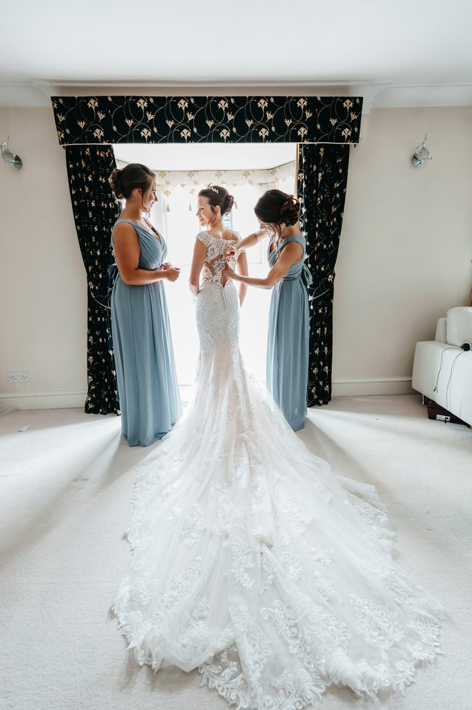 bride helped into wedding dress by bridesmaid