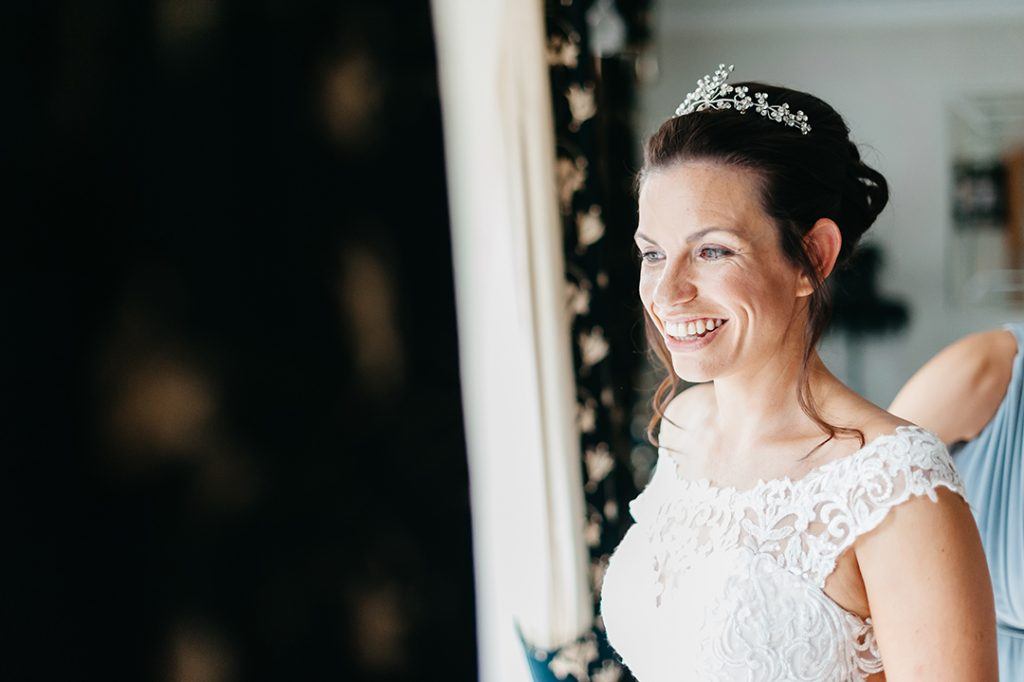 bride smiling out of window in white dress