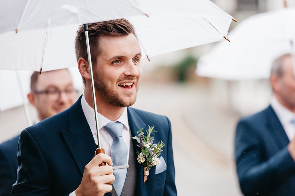 groom in blue suit holding umbrella raining