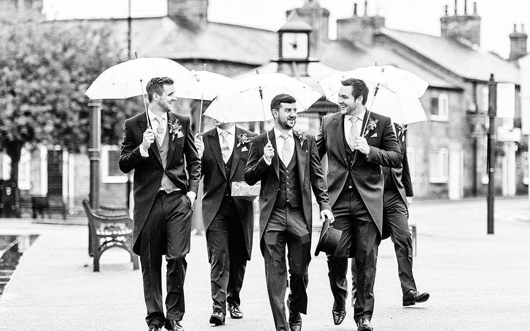 wedding photography coverage of groomsmen holding umbrellas walking