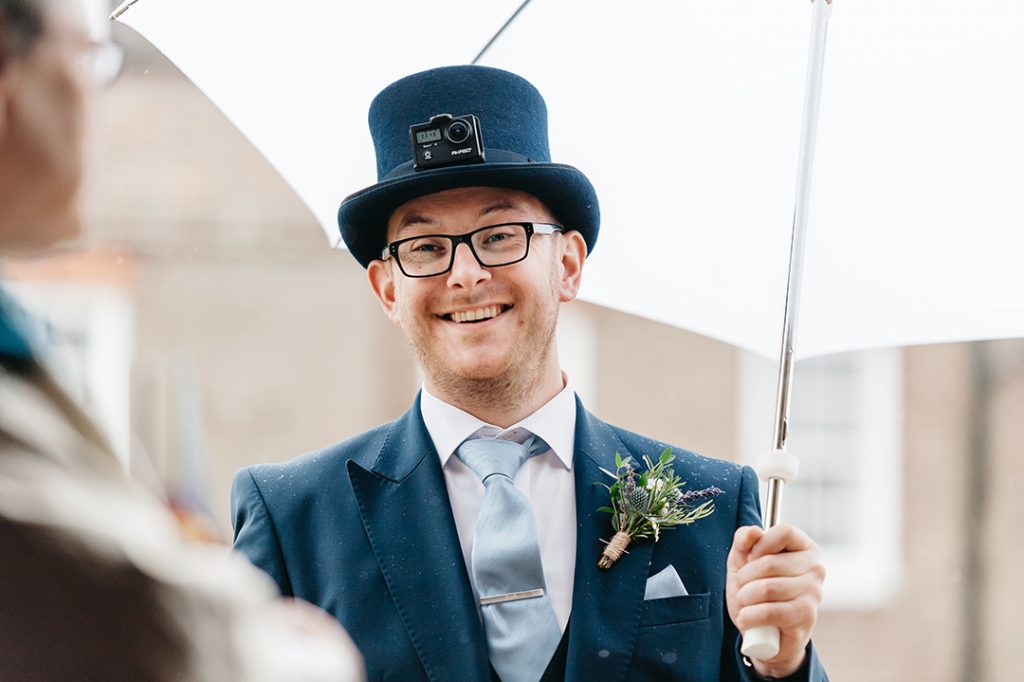 bestman holds umbrella