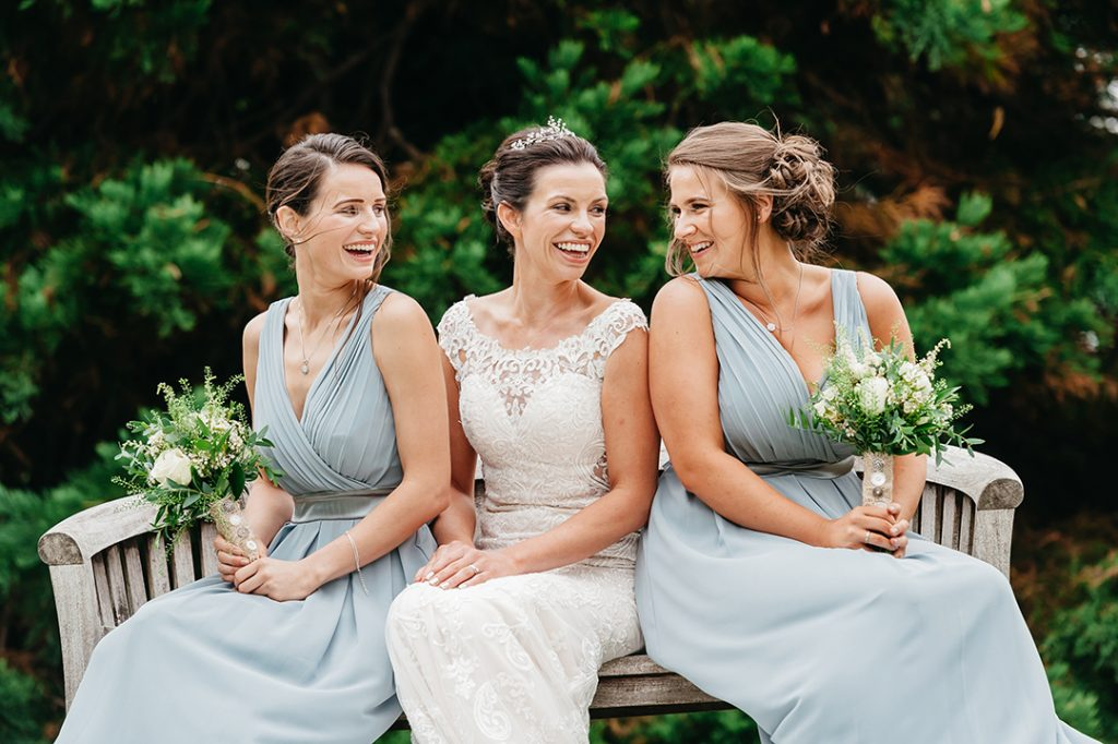bride seated with bridesmaids on bench