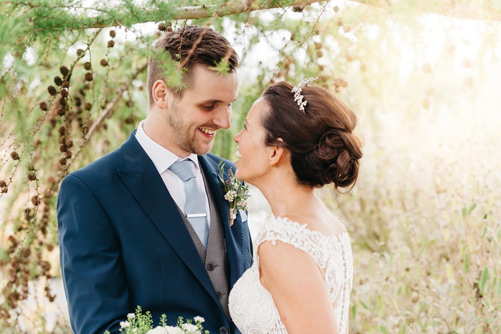 bright image of bride and groom sun flare