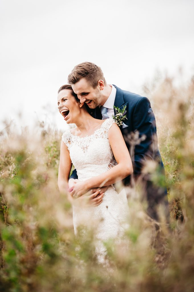 bride hugged by groom in field