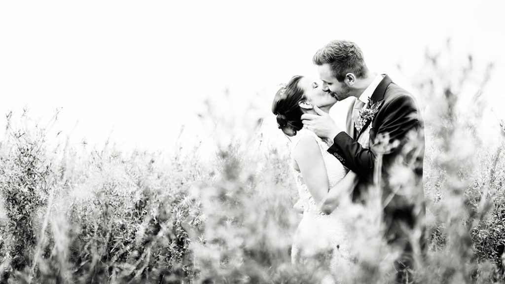 bride and groom embrace and kiss