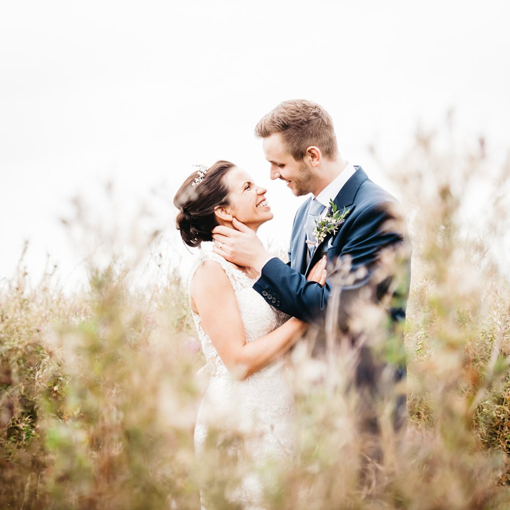 groom laughing at bride in field romantic
