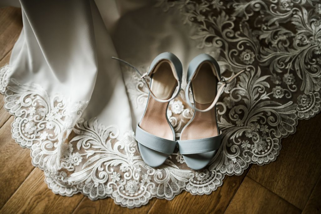 blue wedding shoes on top of wedding dress