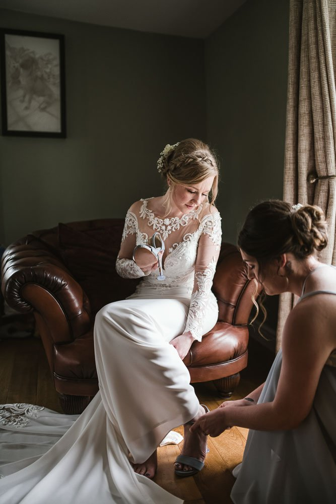 bridesmaid helping bride put on wedding shoes