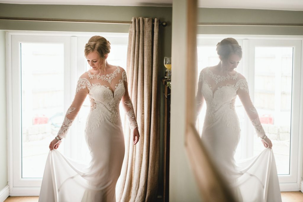 bride holding dress in mirror
