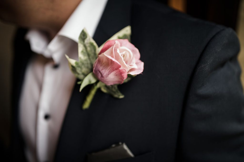 pink flower on groom suit