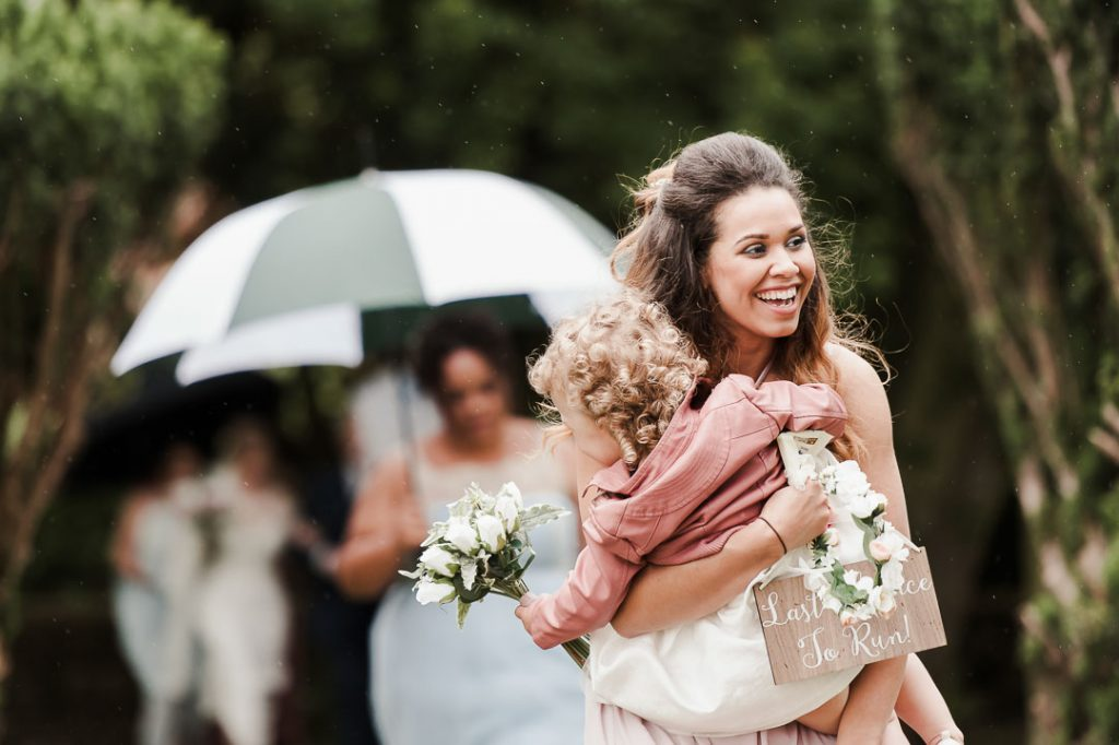 bridesmaid and flower girl walking in rain