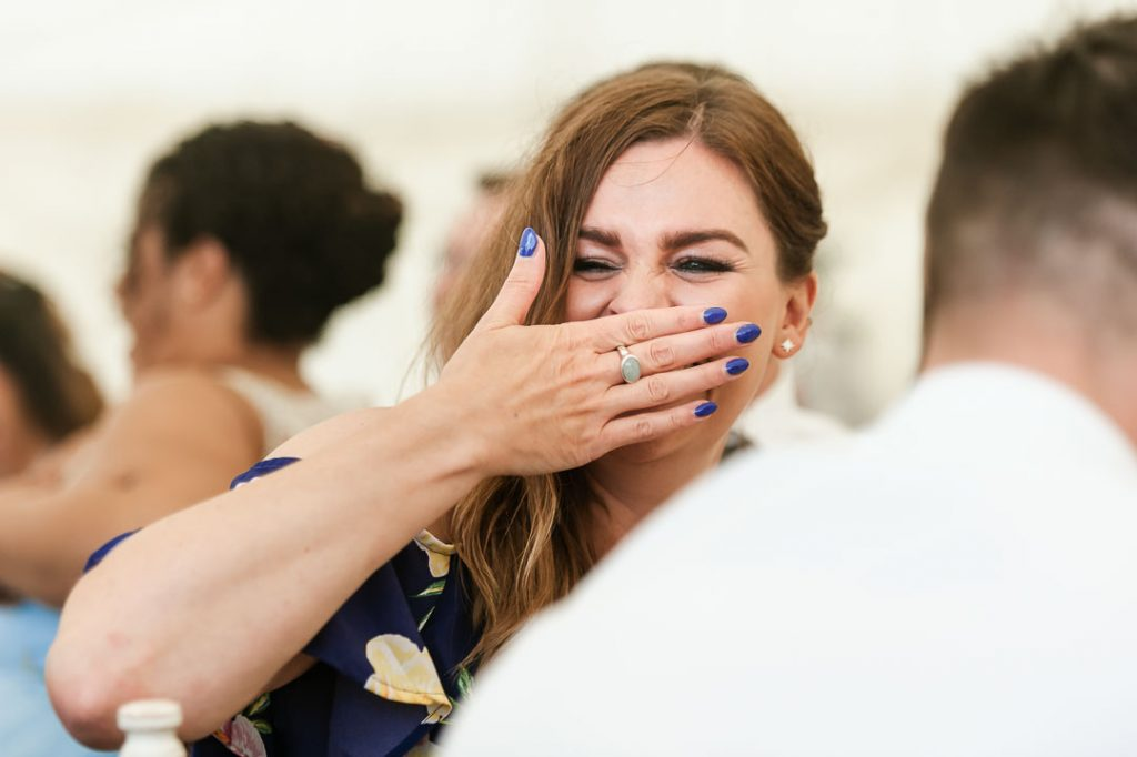 wedding guest woman in blue dress laughing