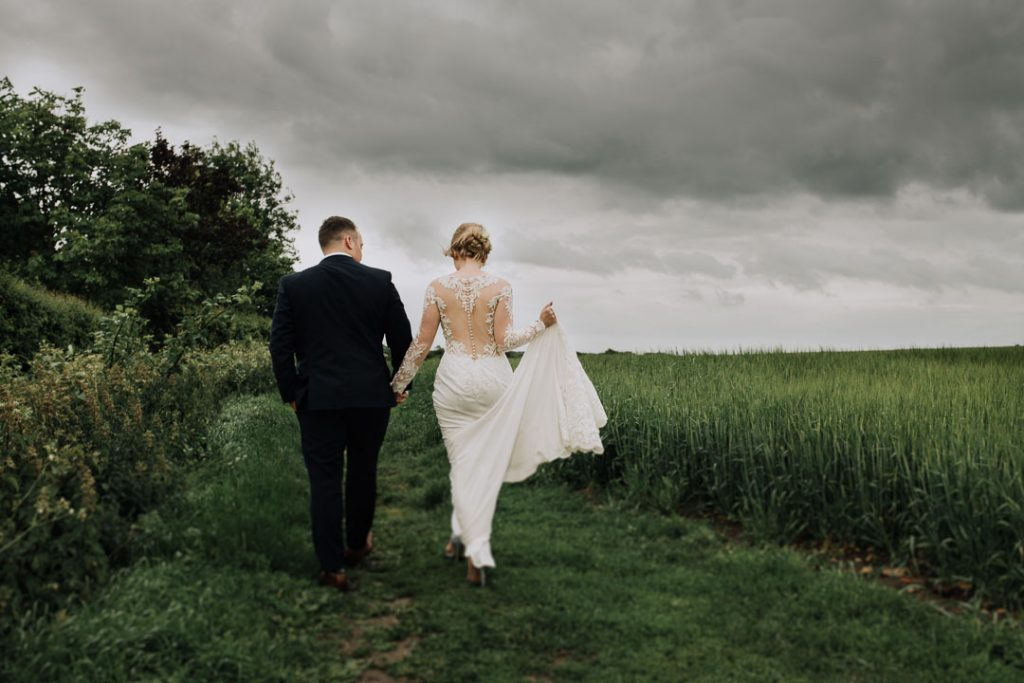 bride and groom walking away in field