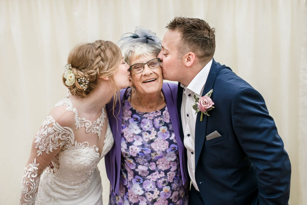 bride and groom kiss old lady