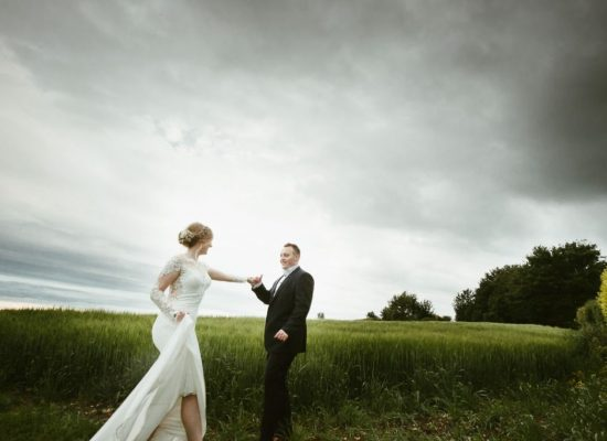 bride and groom in a field holding hands