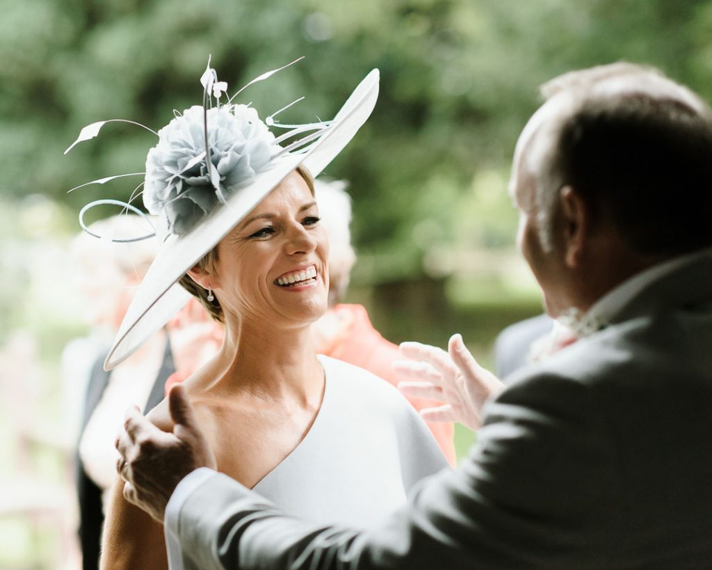 mother of bride in blue hat laughing