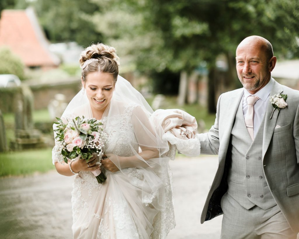 father of bride walking with bride holding dress