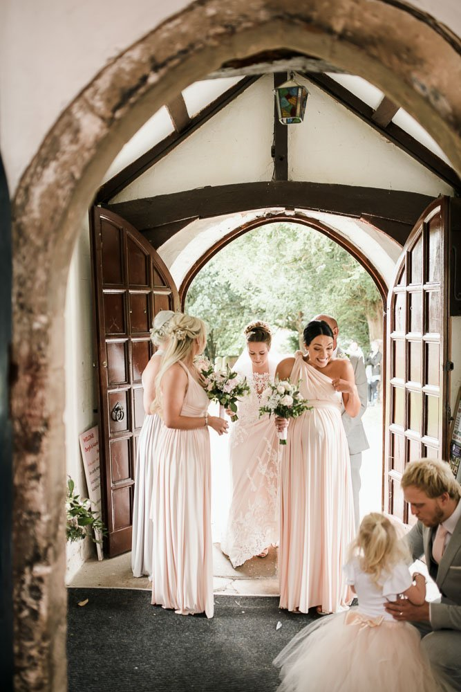 bride entering church with bridesmaids